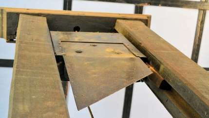 An old, wooden guillotine shows sharp blade.