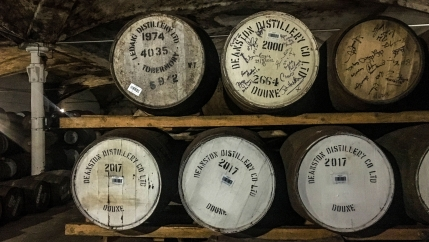 Wooden barrels of Scotch sit on a shelf in a storage area