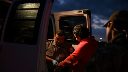 Undocumented migrants are escorted into a transport van after being apprehended by US Border Patrol agents following an illegal crossing of the Rio Grande in Mission, Texas, on Oct. 8, 2019.