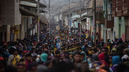 Piura Street in Ayabaca, Peru, is shown filled with people the entire length of the photo with buildings on either side.