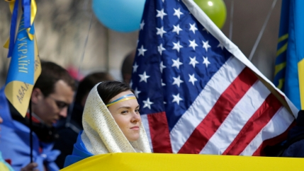 A woman surrounded by US and Ukrainian flags