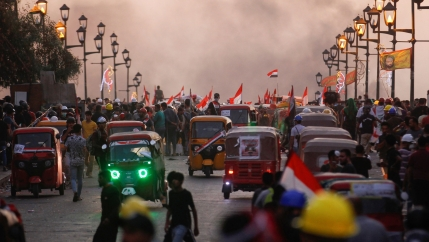Demonstrators and tuk-tuk drivers are seen on a bridge during ongoing anti-government protests, in Baghdad, Iraq, on Nov. 4, 2019.