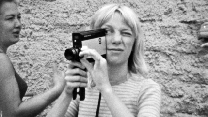 A woman holds a video camera in her hand in a black and white photo