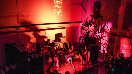 A four-piece punk band is shown playing to a crowd and bathed in red lights.