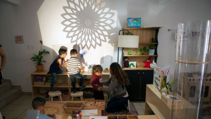 Several children are shown playing with a flower-shaped light projection on a wall.