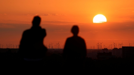 A bright orange sunset is shown in the distance with several wind turbines in the distance and two people in shadow in the nearground.