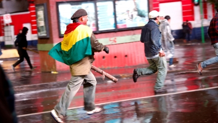 Several people are shown running in the street with one man draped in a Bolivian flag.