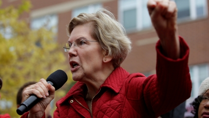 Elizabeth Warren wears a red blazer and speaks with one hand in the air.