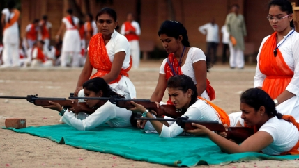 Women lie on a green cloth and practice aiming their guns while wearing red sashes.