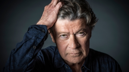 Robbie Robertson looks at the camera posing for a photo