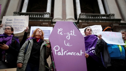 Women hold a coffin prop during a demonstration to protest femicide and violence against women in Paris.