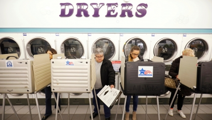 People stand in voting booth casting ballots