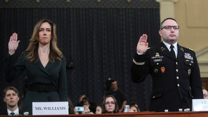 A woman stands with her right hand up, next to a man in military uniform.