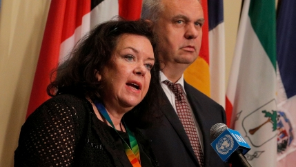 A woman speaks at a podium with a man behind her