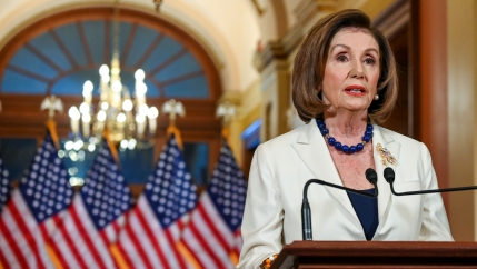 Nancy Pelosi in a white jacket stands at a podium in front of American flags.