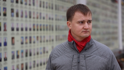 A man stands somberly in front of a wall of small portraits of soldiers