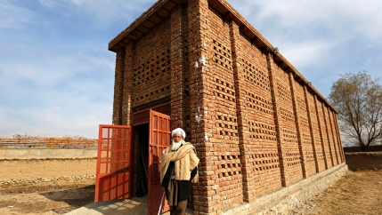 A man stands in front of a brick building in rural setting