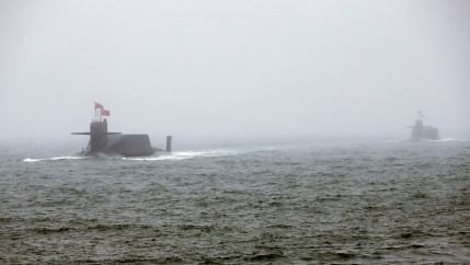 Two Chinese submarines are shown at surface depth and with Chinese flags flying.