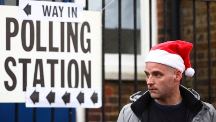 A man is shown wearing a red and white Santa Claus hat and standing next to a white sign with the words 'polling station' printed on it.
