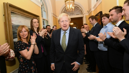 Britain's Prime Minister Boris Johnson is shown walking down a hallway with staff applauding on either side.