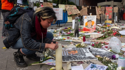 A student leans over a candle at a memorial with lots of photos and paintings