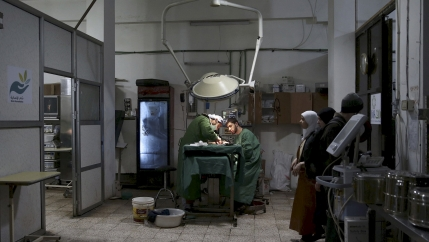 Doctors operate under a dim light in a clinic.