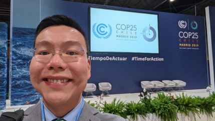 Ben Charles takes a phot of himself in glasses in gray suit against backdrop of COP25 signage