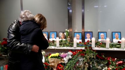 Two people are shown hugging while standing in front of a makeshift memorial for Ukraine Airlines flight that crashed.