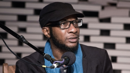 a man wearing glasses and a hat sits behind a microphone