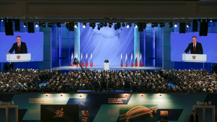 A man speaks from a podium in front of an audience. He is flanked by Russian flags and screens