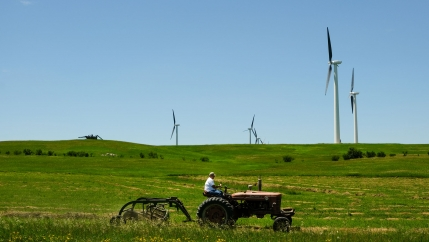 A farm tractor is shown in a large green field with wind turbines in the background.
