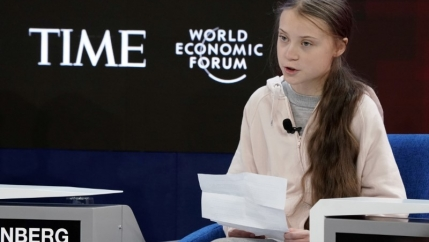 Greta Thunberg sits at the World Economic Forum.