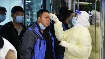 A man wears a mask as he gets checked at airport for virus