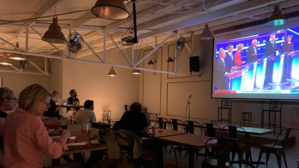 A group of American voters gathered at a BBQ restaurant in Mexico City to watch the Democratic presidential debate broadcast from Charleston, South Carolina, Feb. 25, 2020.