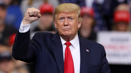 US President Donald Trump is shown wearing a blue jacket and red tie with his right hand raised in a fist.
