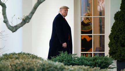 An older white man in a long black coat walks