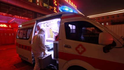An ambulance worker wearing a full body protective suit is shown carrying a suitcase and climbing into an ambulance van.
