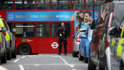 A police officer stands in front of a red London bus