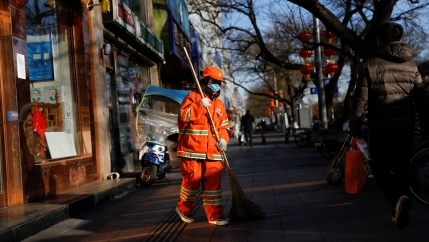 A street cleaner is shown wearing an orange, reflective safety suit and a face mask walks on a sidewalk.