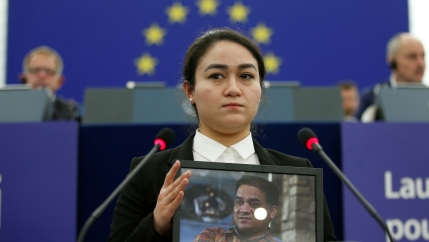 A woman stands with a photo of her father