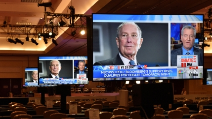 An image of the face of Michael Bloomberg is shown on a large video monitor in an auditorium with empty seats.