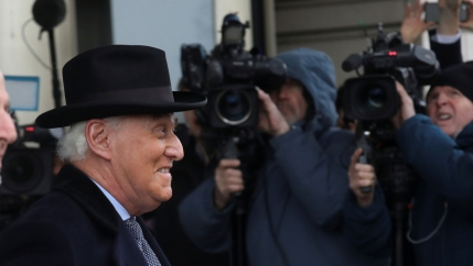 Former Trump campaign adviser Roger Stone is shown wearing a black top hat and overcoat while walking past cameras.