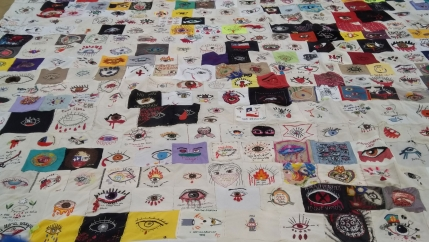 A close-up section of several rows of embroided protest art showing bleeding eyes.