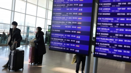 Tourists walk next to the display flight information at Josep Tarradellas Barcelona-El Prat Airport, where cases of novel coronavirus has been confirmed in Barcelona, Spain February 26, 2020.