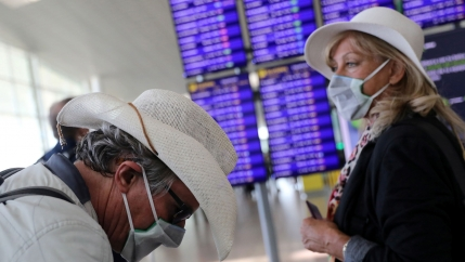 A man is shown hearing a white hat and looking down while wearing a face mask near a woman wearing a white hat and wearing a face mask.