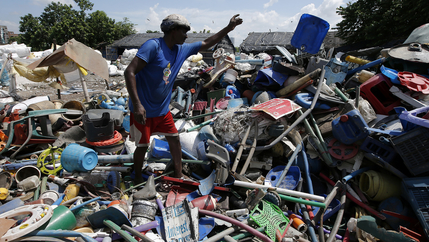 A man picks through a huge heap of plastic trash