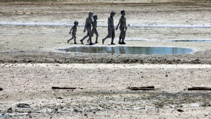 Four young people walk on an island with puddles
