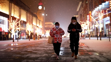 People wearing face masks walk along a street, as China is hit by an outbreak of the new coronavirus, in Beijing, Feb. 5, 2020.