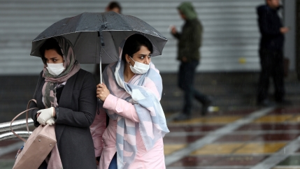Iranian women wear protective masks to prevent contracting coronavirus as they walk in the street in Tehran, Iran, Feb. 25, 2020.
