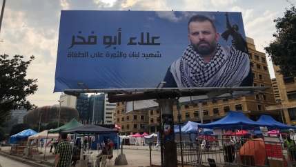 Vendors and civil society tents set up in Martyrs' Square under the photo of man who was killed during a roadblock in a suburb of Beirut.